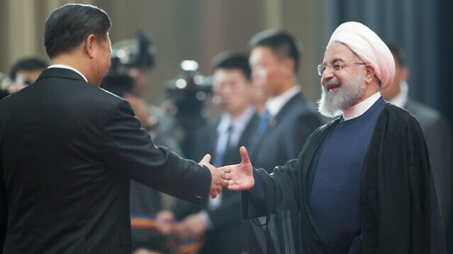 Chinese President Xi Jinping, left, greets Iranian President Hassan Rouhani at the Shanghai Cooperation Organization (SCO) Summit in Qingdao in eastern China's Shandong Province, Sunday, June 10, 2018. China will seek to further promote its economic links with Central Asia during this weekend's summit of the China and Russia-dominated SCO. (AP Photo/Alexander Zemlianichenko)