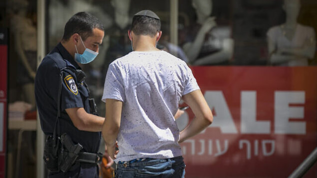 A Jerusalemite young man gets a fine from Israeli police officers after she was seen walking in the street with no mask  in Jerusalem City center on July 03, 2020. Israel has seen a spike of new COVID-19 cases bringing the authorities to reimpose restrictions to halt the spread of the virus. Photo by Olivier Fitoussi/Flash90 *** Local Caption *** ירושלים קורונה  וירוס מירכז העיר דוחות משטרה