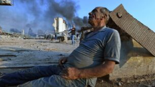 A wounded man sits on the ground waiting for aid at Beirut's port following a massive explosion that hit the heart of the Lebanese capital on August 4, 2020. - Rescuers searched for survivors in Beirut on August 5 after a cataclysmic explosion at the port sowed devastation across entire neighbourhoods, killing more than 100 people, wounding thousands and plunging Lebanon deeper into crisis. (Photo by - / AFP)