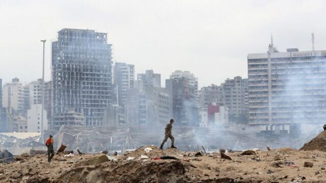 A soldier walks at the devastated site of the explosion in the port of Beirut on August 6, 2020 two days after a massive explosion devastated the Lebanese capital in a disaster that has sparked grief and fury. - French President visited shell-shocked Beirut on August 6, pledging support and urging change after a massive explosion devastated the Lebanese capital in a disaster that left 300,000 people homeless. (Photo by Thibault Camus / POOL / AFP)