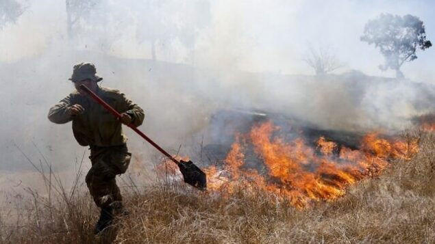 An Israeli soldier battles a blaze in a field close to the southern Israeli kibbutz of Nir Am near the border with the Gaza Strip on August 23, 2020, after it was reportedly set off by incendiary kites flown from the Palestinian enclave. (Photo by menahem kahana / AFP)