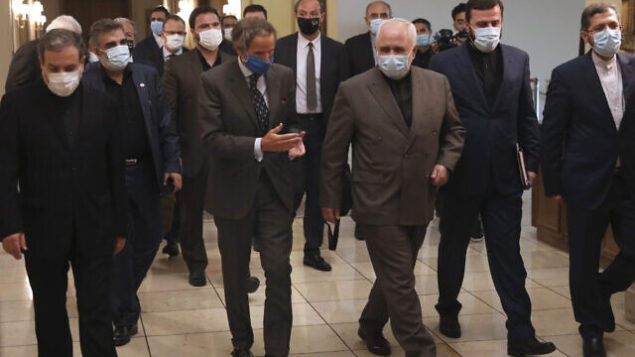 Director General of International Atomic Energy Agency, IAEA, Rafael Mariano Grossi, center left, speaks with Iran's Foreign Minister Mohammad Javad Zarif, center left, before a meeting in Tehran, Iran, Tuesday, Aug. 25, 2020. Grossi arrived in Iran on Monday to press for access to sites where authorities are thought to have stored or used undeclared nuclear material. (AP Photo/Vahid Salemi)