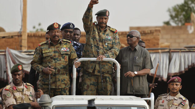 """Sudanese Gen. Abdel-Fattah Burhan, head of the military council, waves to his supporters upon his arrival to attend a military-backed rally, in Omdurman district, west of Khartoum, Sudan, Saturday, June 29, 2019. Sudan's ruling military council on Saturday warned protest leaders of """"destruction or damage"""" ahead of planned mass rallies over the weekend calling for civilian rule over two months after the military ouster of autocratic president Omar al-Bashir. (AP Photo/Hussein Malla)"""