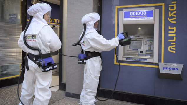 Cleaning workers disinfect an ATM at a bank in Ramat Gan.  June 3, 2020. Photo by Flash90 *** Local Caption *** çéèåé áð÷