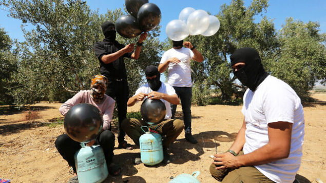 Palestinian men prepare a flammable object to be flown toward Israel, near the Israel-Gaza border, in the eastern part of the Gaza Strip, August 10, 2020. Photo by Abed Rahim Khatib/Flash90 *** Local Caption *** פלסטינים רצועת עזה גבול ישראל בלונים בלוני תבערה