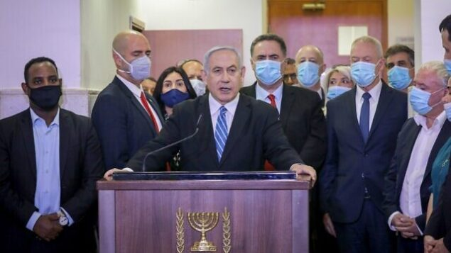 Israeli Prime Minister Benjamin Netanyahu delivers a statement before entering a courtroom at the district court of Jerusalem on May 24, 2020, during the first day of his corruption trial. - Fresh from forming a new government after more than 500 days of electoral deadlock, Netanyahu is expected to begin a new battle in the Jerusalem District Court -- to stay out of prison. The 70-year-old was scheduled to appear at a court hearing to formally confirm his identity to judges, after being indicted in January for bribery, fraud and breach of trust. (Photo by Yonathan SINDEL / POOL / AFP)