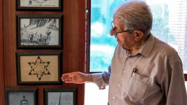 Omar Farhadi, an elderly Iraqi Kurd points to a frame showing a stylized hexagram, or a Star of David, hanging in a room dedicated to famous Jewish Kurdish art teacher and painter Daniel Kassab, at the Museum of Education in Arbil's oldest primary school, in the capital of the autonomous Kurdish region of northern Iraq, on July 5, 2020. - Jews were historically Iraq's second-largest religious sect, comprising 40 percent of Baghdad's population according to a 1917 census. But since the creation of Israel in 1948, regional tensions skyrocketed and anti-Semitic campaigns took hold, pushing most of Iraq's Jews to flee. Today, Iraqis have fond memories of Jewish friends and neighbours, including 82-year-old Farhadi, whose father owned a shop in a Jewish-majority district of Arbil. (Photo by SAFIN HAMED / AFP)