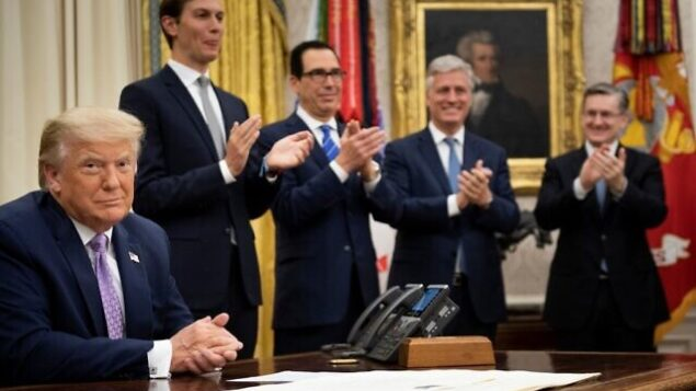 """(L-R, rear) Senior Advisor Jared Kushner, US Secretary of the Treasury Steven Mnuchin and National Security Advisor Robert O'Brien clap for US President Donald Trump (L) after he announced an agreement between the United Arab Emirates and Israel to normalize diplomatic ties, the White House August 13, 2020, in Washington, DC. - Trump on Thursday made the surprise announcement of a peace agreement between Israel and the United Arab Emirates. The normalization of relations between the UAE and Israel is a """"HUGE breakthrough"""" Trump tweeted, calling it a """"Historic Peace Agreement between our two GREAT friends."""" (Photo by Brendan Smialowski / AFP)"""