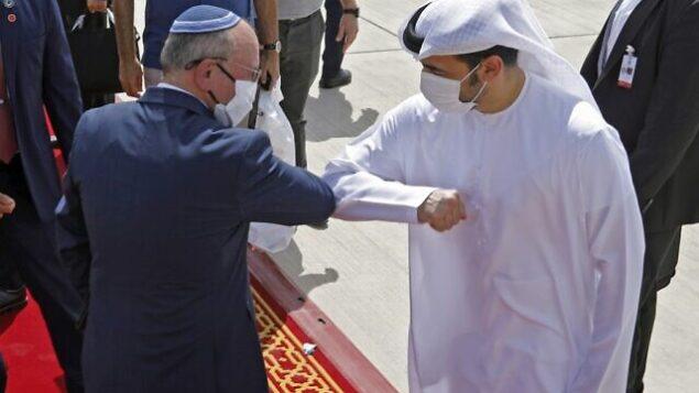 Israeli National Security Advisor Meir Ben-Shabbat elbow bumps with an Emirati official ahead of boarding the plane before leaving Abu Dhabi, United Arab Emirates September 1, 2020. REUTERS/Nir Elias/Pool (Photo by NIR ELIAS / POOL / AFP)