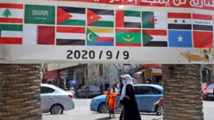 """A banner showing the flags of Arab countries and reading """"History will only glorify those loyal to Palestine"""" is seen during a rally against the UAE-Israel normalisation deal in the occupied West Bank city of Nablus on September 9, 2020, as Arab foreign ministers meet. (Photo by JAAFAR ASHTIYEH / AFP)"""