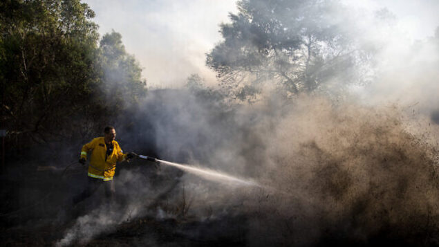 A firefighters attempts to extinguish a fire started by an incendiary device launched from the Gaza Strip, in Kibbutz Kfar Aza on the border with Gaza, Monday, Aug. 24, 2020. Militants affiliated with Hamas have launched scores of incendiary balloons into southern Israel in recent weeks in a bid to pressure Israel to ease the blockade imposed since Hamas took control of the territory in 2007. (AP Photo/Ariel Schalit)