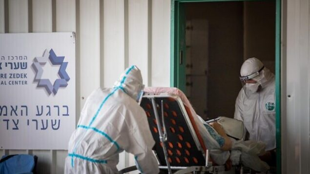 "Magen David Adom workers wearing protective clothing outside the coronavirus unit at Shaare Zedek hospital in Jerusalem on September 10, 2020. Photo by Yonatan Sindel/Flash90 *** Local Caption *** קורונה בית חולים שערי צדק וירוס לבן לבושים מפנים מד""א"