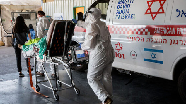 "Magen David Adom workers wearing protective clothing outside the coronavirus unit at Shaare Zedek hospital in Jerusalem on September 14, 2020. Photo by Nati Shohat/Flash90 *** Local Caption *** קורונה בית חולים שערי צדק וירוס לבן לבושים מפנים מד""א"