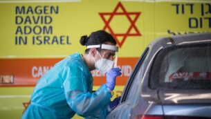 Shaare Zedek Medical team member wearing protective gear takes a swab from a woman to test for the coronavirus disease (COVID-19), outside the coronavirus unit at Shaare Zedek hospital in Jerusalem on September 24, 2020. Photo by Yonatan Sindel/Flash90 *** Local Caption ***