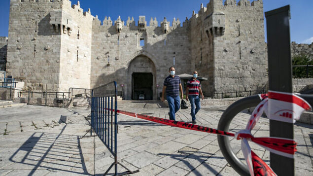 Jerusalemites walk on the empty plazza of the Damascus Gate in Jerusalem, on September 25, 2020. Israel has seen a spike of COVID-19 cases bringing the authorities to reimpose a nationwide lockdown. Photo by Olivier Fitoussi/Flash90 *** Local Caption ***
