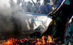 تصویر: دانشجویان سودانی در مقابل مقر سازمان ملل در خارطوم، در حال آتش زدن پرچم اسرائیل در تظاهرات علیه حمله هوایی اسرائیل به غزه، سودان، ۲۹ دسامبر ۲۰۰۸. (AP/Abd Raouf)