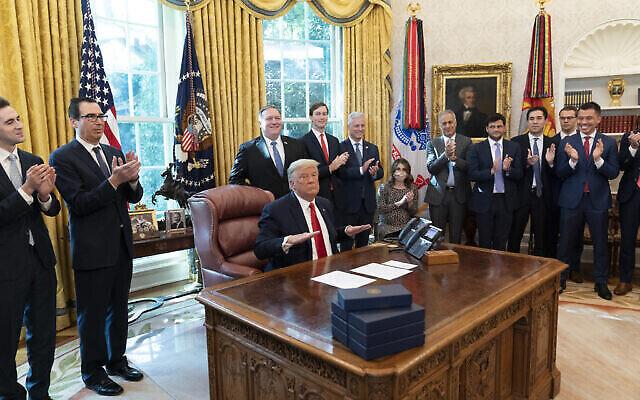 تصویر: دونالد ترامپ رئیس جمهور ایالات متحده، پس از پایان تماس تلفنی با رهبران سودان و اسرائیل؛ استیون منوخین وزیر خزانه داری، دومی از چپ، مایک پمپئو وزیر خارجه، جراد کوشنر مشاور ارشد کاخ سفید، رابرت اوبرایان مشاور امنیت ملی، و دیگران حین کف زدن، اتاق بیضی کاخ سفید، ۲۳ اکتبر ۲۰۲۰، واشنگتن.  (AP Photo/Alex Brandon)