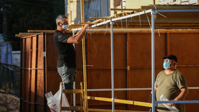 """Jews building a """"Sukka"""" for the upcoming Jewish holiday of Sukkot, in the streets of the northern Israeli city of Tzfat, September 29, 2020. Photo by David Cohen/Flash90 *** Local Caption ***"""