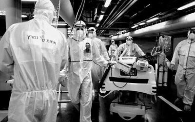 تصویر: کارکنان مگان دیوید آدوم با لباس و تجهیزات حفاظتی در مقابل واحد ویروس کرونای بیمارستان شعاری تصدک در اورشلیم، ۱۱ اکتبر ۲۰۲۰. (Nati Shohat/Flash90)