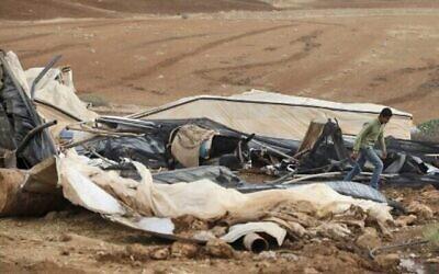 تصویر: پس از آنکه سربازان اسرائیلی خیمه هایی را در شرق روستای توباس، در اراضی اشغالی کرانه باختری، منهدم کردند، یک فلسطینی بدوی خر خود را از مقابل بقایای خیمه تخریب شدهٔ خود عبور میدهد، ۳ نوامبر ۲۰۲۰.  (Photo by JAAFAR ASHTIYEH / AFP)