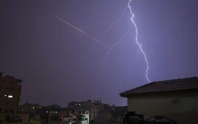 تصویر: در عکسی که از شهر غزه در ۱۵ نوامبر ۲۰۲۰ گرفته شده، همزمان با رعد و برق، درخشش نور ناشی از پرتاب راکت، بر فراز ساختمان مشاهده میشود. (MOHAMMED ABED / AFP)
