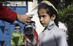 تصویر: درجه تب کودکان فلسطینی، که بعلت پاندمی کوئید ۱۹ ماسک زده اند، هنگام ورود به یک پیش-دبستانی در شهر غزه اندازه گیری می شود، ۲۳ نوامبر ۲۰۲۰. (MOHAMMED ABED / AFP)