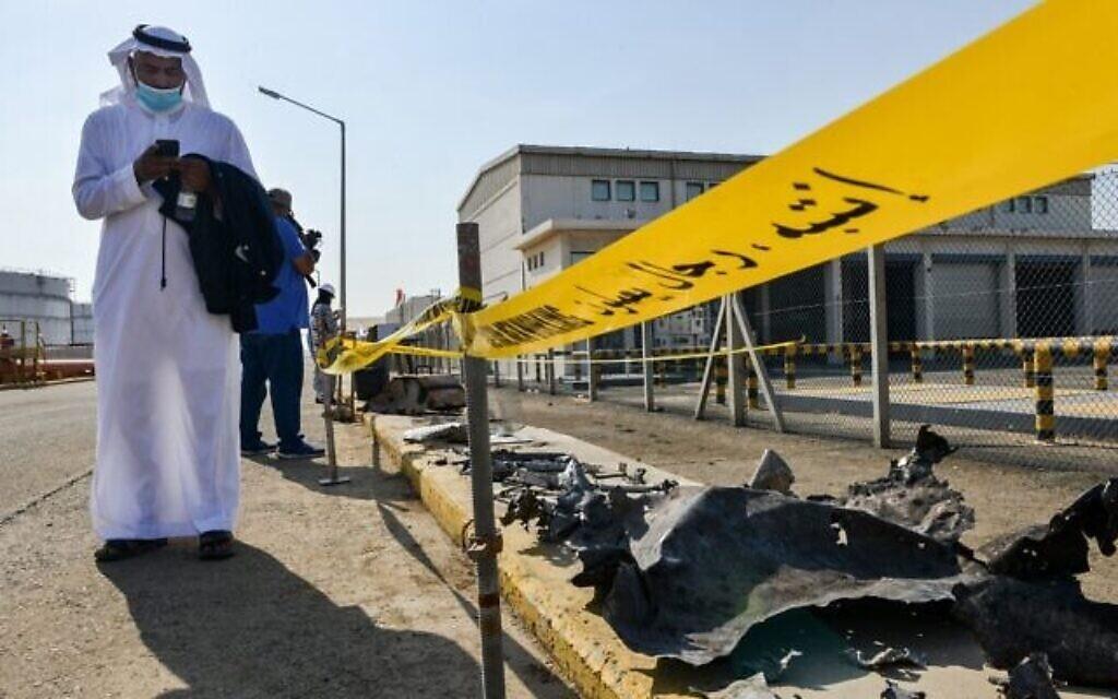 یک مرد، که بعلت پاندمی کوئید ۱۹ ماسک به صورت دارد، پس از حمله ۲۴ نوامبر ۲۰۲۰ به تأسیسات نفتی آرامکوی سعودی، در شهر جده، واقع در دریای سرخ، عربستان، ایستاده کنار خرابه های بنا، روی گوشی خود جستجو می کند. (FAYEZ NURELDINE / AFP)