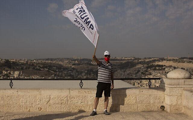 تصویر: یک حامی اسرائیلی دونالد ترامپ رئیس جمهور ایالات متحده با پرچم کارزار انتخاباتی در دست، در راهپیمایی انتخابات مجدد وی در یک محل تفریحی مُشرف به اورشلیم، ۲۷ اکتبر ۲۰۲۰. (Maya Alleruzzo/AP)