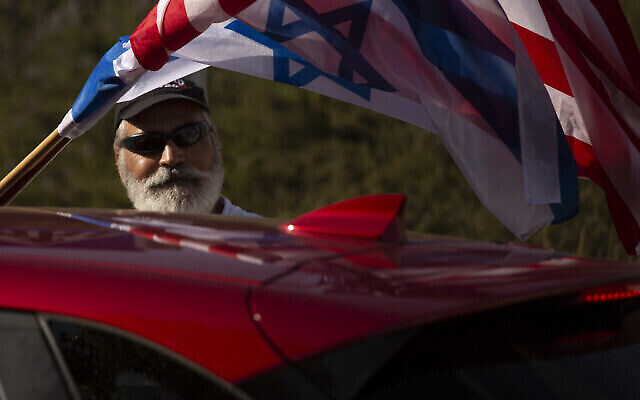 تصویر: حامی اسرائیلی دونالد ترامپ رئیس جمهور ایاالت متحده در راهپیمایی مقابل سفارت ایالات متحده در اورشلیم،  پرچم های آمریکا و اسرائیل را از پنجره ماشین به اهتزاز درآورده، ۲۷ اکتبر ۲۰۲۰. (AP Photo/Maya Alleruzzo)
