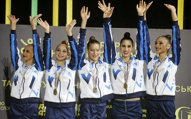تصویر: تیم ژیمناستیک ریتمیک اسرائیل پیش از دریافت مدال طلای سی و ششمین مسابقات قهرمانی ژیمناستیک ریتمیک در کی-یف،اوکراین، از روی سکو دست تکان می دهد، ۲۷ نوامبر ۲۰۲۰. (AP Photo/Efrem Lukatsky)
