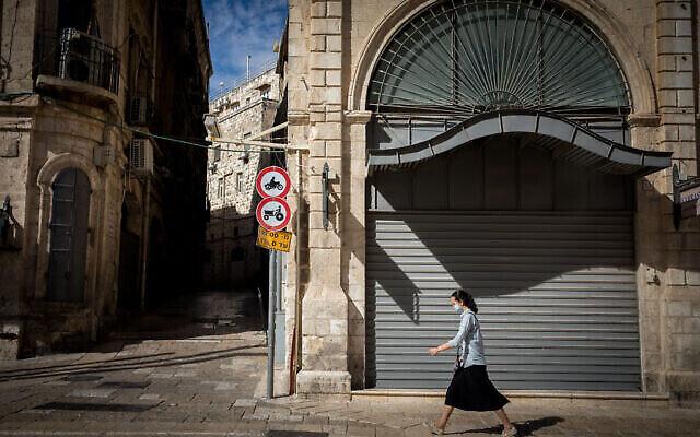 تصویر: در طول تعطیل سراسری در اسرائیل، زنی از مقابل فروشگاهی بسته در نزدیکی گذرگاه جفا در شهر قدیم اورشلیم میگذرد، ۱۳ اکتبر ۲۰۲۰. (Nati Shohat/Flash90)