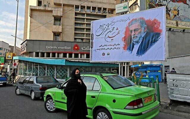 تصویر: زنی از کنار بیلبوردی که به افتخار دانشمند هسته ای مقتول، محسن فخری زاده در تهران، پایتخت ایران نصب شده، می گذرد، ۳۰ نوامبر ۲۰۲۰. (ATTA KENARE/AFP)