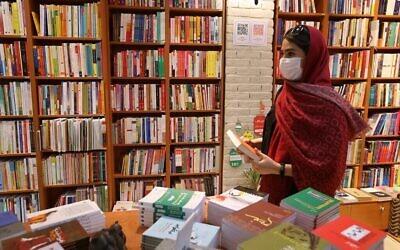 تصویر: زنی در یک کتابفروشی در خیابان انقلاب، تهران، پایتخت ایران، کتابی برداشته و در دست گرفته است، ۸ سپتامبر ۲۰۲۰. (ATTA KENARE / AFP)
