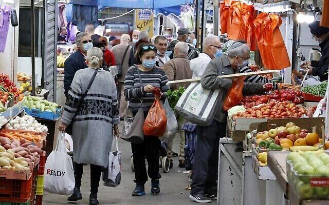 تصویر: مردم اسرائیل که بعلت پاندمی کوئید ۱۹ ماسک به صورت دارند، در بازار مرکزی نتانیا، پیش از شروع تعطیل سراسری سوم، به خرید مشغول اند، ۲۷ دسامبر ۲۰۲۰. (JACK GUEZ / AFP)