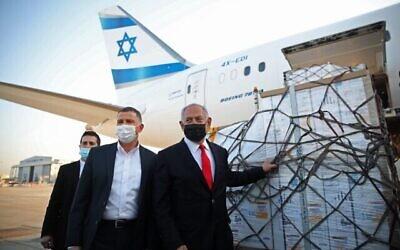 تصویر: بنیامین نتانیاهو نخست وزیر، راست، و یولی ادلشتاین وزیر بهداشت، وسط، در مراسمی که برای ورود هواپیمای حامل محموله واکسن ضدکرونای Pfizer-BioNTech  در فرودگاه بن گوریون، نزدیک شهر تل آویو اسرائیل در ۱۰ ژانویه ۲۰۲۱ برگزار شد. (Motti MILLROD / POOL / AFP)