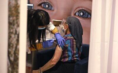 تصویر: به یک زن اسرائیلی در مرکز تلقیح «کوپات هولیم موحیدیت» اورشلیم، واکسن کوئید ۱۹ تزریق می شود، ۱۲ ژانویه ۲۰۲۱. (MENAHEM KAHANA / AFP)