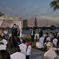 تصویر: یک خاخام در کنار سایبان سنّتی یهودیان، حین اجرای مراسم عقد و عروسی زوج اسرائیلی، نائومی آزیراد، چپ، نشسته زیر سایبان، و سیمون دیوید بنخامو، در هتلی در دوبی، امارات متحد عربی، ۱۷ دسامبر ۲۰۲۰.  (Kamran Jebreili/AP)