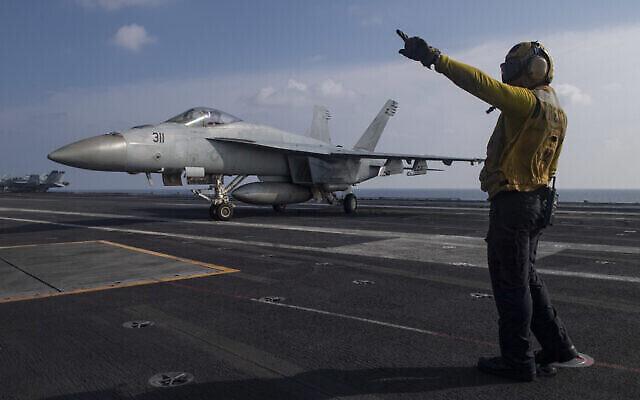 تصویر: در عکسی از نیروی دریایی ایالات متحده ، هواپیمای رتبهٔ ۳ مارنل ماگلاسانگ  Boatswain's Mate از لا پونته، کالیفرنیا ، یک F / A-18E Super Hornet را در عرشه پرواز ناو هواپیمابر USS Nimitz  در خلیج فارس هدایت می کند، جمعه ۲۷ نوامبر ۲۰۲۰. طبق اظهار پنتاگون،  Nimitz برای حمایت و کمک به خروج سربازان از افغانستان و عراق به خاورمیانه بازگشته است.  (Mass Communication Specialist 3rd Class Cheyenne Geletka/U.S. Navy via AP)