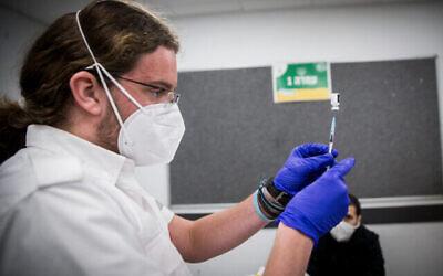 تصویر: یکی از کارکنان درمانی حین آماده کردن واکسن کوئید ۱۹ در کیریات یئاریم، ۲۵ ژانویه ۲۰۲۱.  (Yonatan Sindel/Flash90)