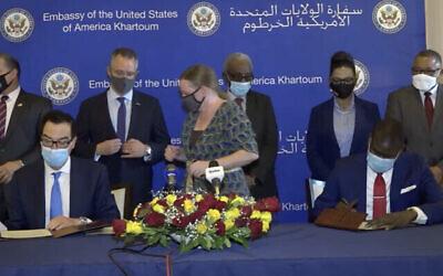 تصویر: استیون منوخین، وزیر خزانه داری ایالات متحده، چپ، و نصرالدین عبدالبری، وزیر دادگستری سودان توافق ابراهیم را در پایتخت سودان، خارطوم، امضا کردند، ۶ ژانویه ۲۰۲۱. (Screen capture: Facebook)