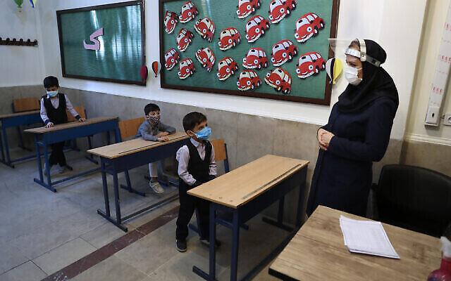 تصویر: دانش آموزان و آموزگارشان در کلاس درس، پس از مراسم گشایش مدرسه هشترودی در تهران، ایران، ۵ سپتامبر ۲۰۲۰. (AP Photo/Vahid Salemi)