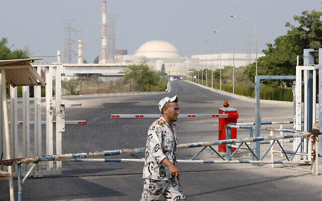 تصویر: در عکسی از ۲۰ اوت ۲۰۱۰، یکی گارد امنیتی ایران در مقابل دروازه نیروگاه اتمی بوشهر، درست خارج شهر بوشهر، ۷۵۰ مایل (۱۲۴۵ کیلومتر) جنوب تهران، پایتخت ایران، قدم می زند، و بنای رآکتور در پسزمینه قابل مشاهده است. (AP Photo/Vahid Salemi)