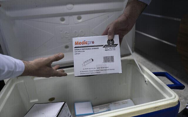 تصویر تزئینی: کادر درمانی فلسطینی در حال باز کردن بسته های واکسن های کوئید ۱۹ مادرنا و دیگر تجهیزاتی که برای کارکنان خط اول درمان ارسال شده، در محل وزارت بهداشت، بیت اللحم، کرانه باختری، ۳ فوریه ۲۰۲۱. پیش از این، تشکیلات خودگردان فلسطینیان، در اولین مورد معلوم، پس از دریافت چندهزار دوز واکسن مادرنا از اسرائيل اقدام به تزریق واکسن کرونا کرده بود. (AP Photo/Nasser Nasser)