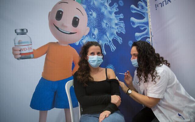 تصویر: در سالن ورزشی در «حاد حا شارون»، ناحیه مرکزی اسرائیل، که تبدیل به مرکز تلقیح واکسن شده، به زنی واکسن کوئید ۱۹ تزریق می شود، ۲ فوریه ۲۰۲۱. (Miriam Alster/Flash90)