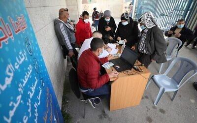 تصویر: یکی از کارکنان تشکیلات خودگردان فلسطینیان در کرانه باختری نام خود را برای تزریق واکسن کرونا ثبت می کند؛ ۲۱مارس ۲۰۲۱. (WAFA)