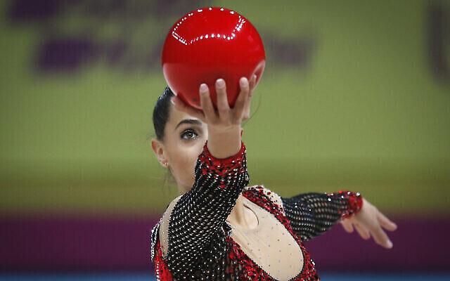 تصویر: «لیونی اشرام»، ژیمناست اسرائیلی حین اجرا با توپ در سی و نهمین مسابقات قهرمانی ژیمناستیک ریتمیک در کی-یف، اوکراین، ۲۹ نوامبر ۲۰۲۰. (AP Photo/Efrem Lukatsky)