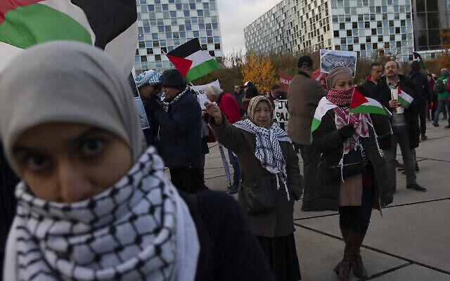 تصویر: تظاهرات کنندگان با بانر و پرچم فلسطینیان در مقابل دیوان عالی لاهه، آی.سی.سی.، خواهان تعقیب قضایی جنایات جنگی ارتش اسرائیل در دیوان لاهه، هلند، ۲۹ نوامبر ۲۰۱۹. (AP Photo/Peter Dejong)
