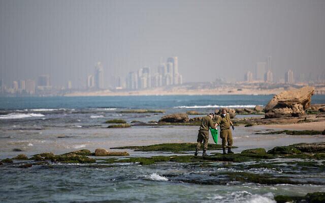 تصویر: در پی نشت نفت در آبهای ساحلی اسرائیل که بخش بزرگی از کنارهٔ دریا آلوده کرد، سربازان در حال زدودن قیر از ساحل پالماخیم هستند؛ ۲۲ فوریه ۲۰۲۱. (Yonatan Sindel/Flash90)`