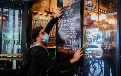 تصویر: کارگری آگهی استخدام رستورانی در تل آویو را روی شیشه می چسباند؛ ۳ مارس ۲۰۲۱.  (Avshalom Sassoni/Flash90)