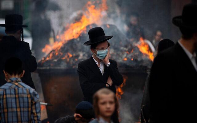 مردان و کودکان ارتدکس افراطی در شهر «بنی براک»، نزدیک تل آویو، اقلام مخمردار را در استقبال عید پسح در آتش می ریزند، ۲۶ مارس ۲۰۲۱. (AP Photo/Oded Balilty)